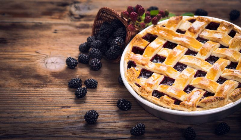 A white dish that contains a blackberry and ginger pie with blackberries scattered on the table next to it