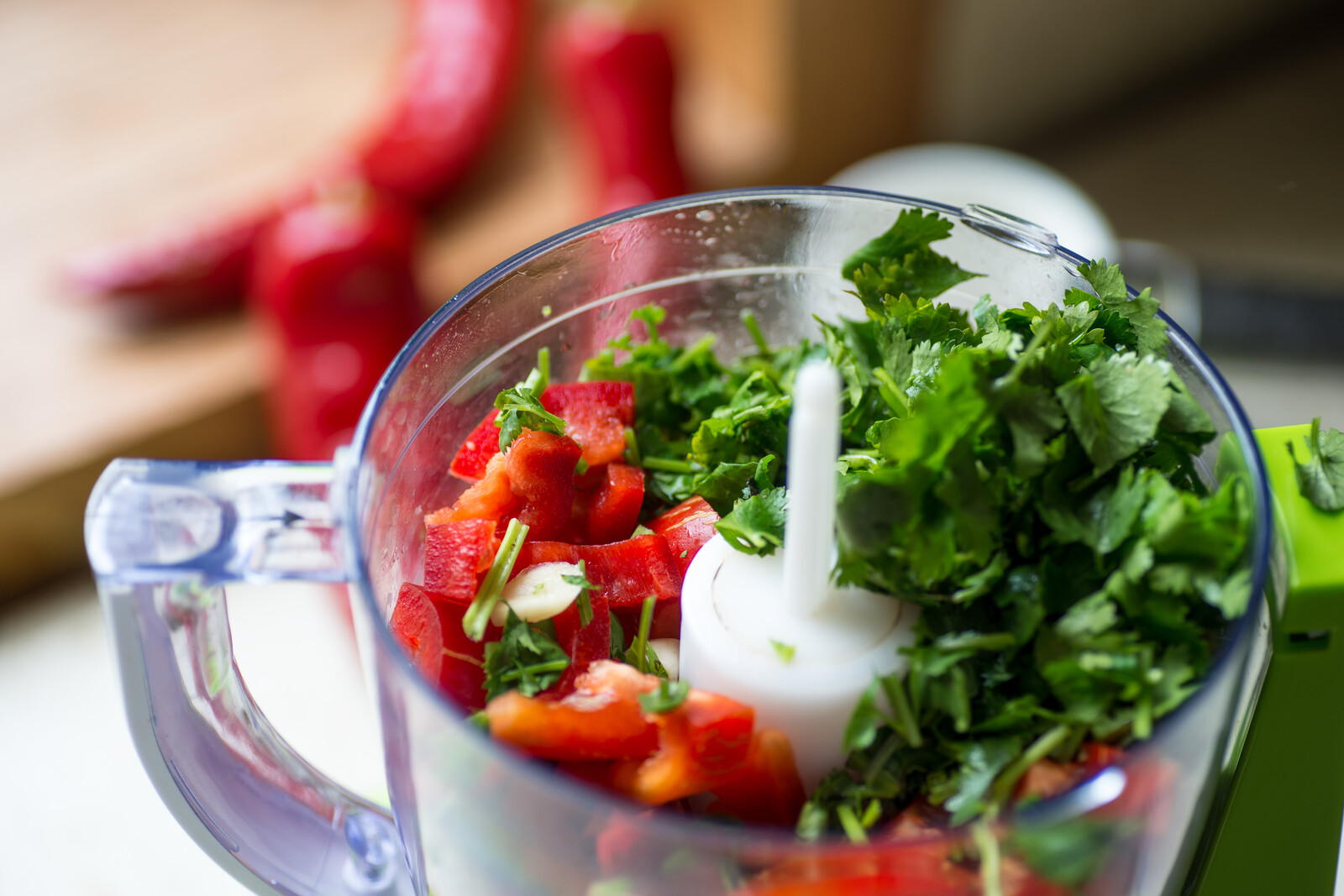 Blender with fresh bell pepper and cilantro on a kitchen table ready for juicing
