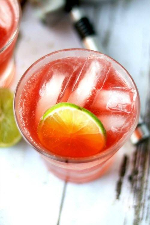 A top down image of a glass with a pink cocktail, lime and ice