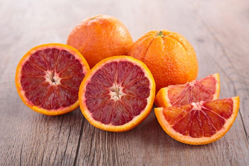 Blood oranges on a table where some have been sliced open