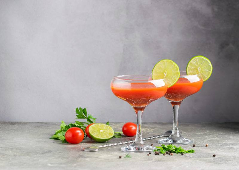 Two bloody Maria cocktails in glasses with sliced lime