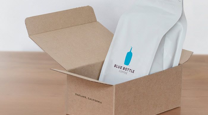 A cardboard box with a white bag of coffee from Blue Bottle coffee