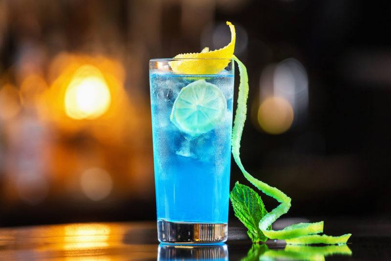 A Blue lagoon cocktail in a tall glass with an out-of-focus bar in the background