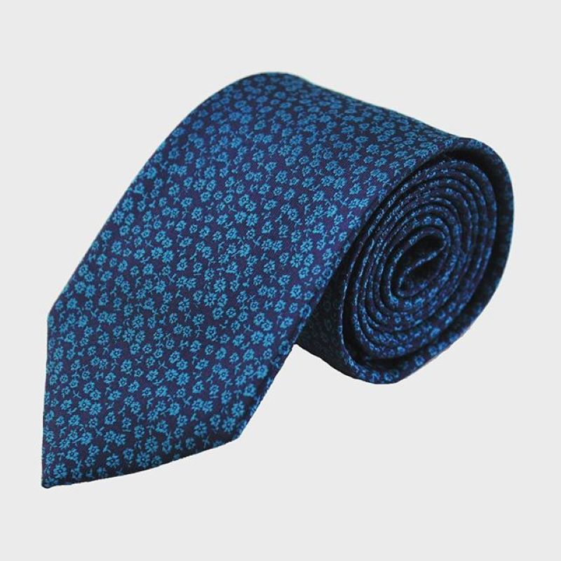 Blue on blue flowered rolled up tie with white background