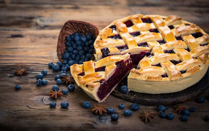 A large blueberry lattice pie with a piece cut out of it, next to a scoop of blueberries