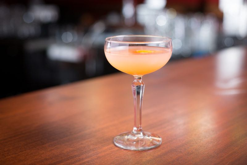 A blushing Betty cocktail in a small glass on a table