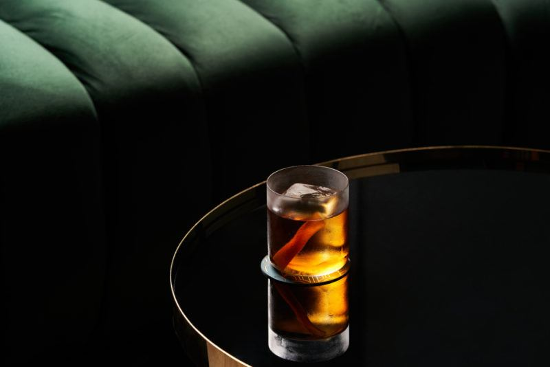 A Bobby Burns cocktail on atable at a restaurant in the dark
