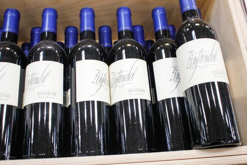 A crate of zinfandel wine in bottles with white labels and blue tops