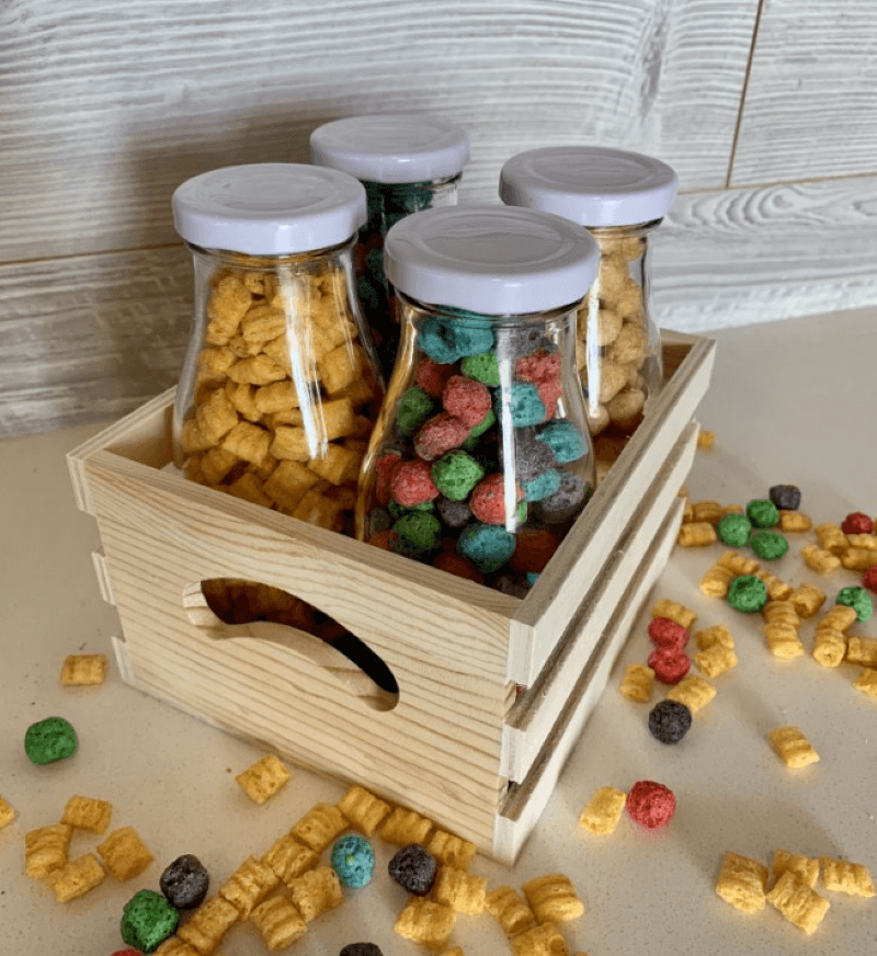 4 milk Bottles of cereal in a crate with cereal scattered on the table around the crate