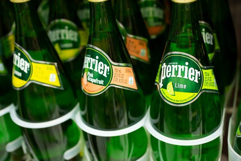 9 bottles of flavored Perrier water in the fridge in a grocery store