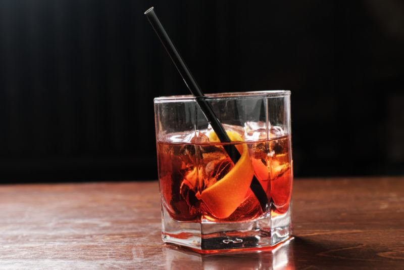 A Boulevardier cocktail with a straw in an old fashioned glass