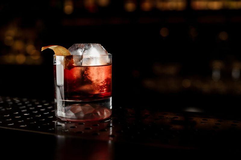 A Boulevardier cocktail on a black bar