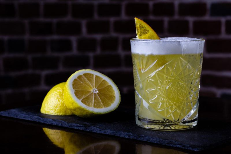 A bourbon sour cocktail in a glass with a sliced lemon