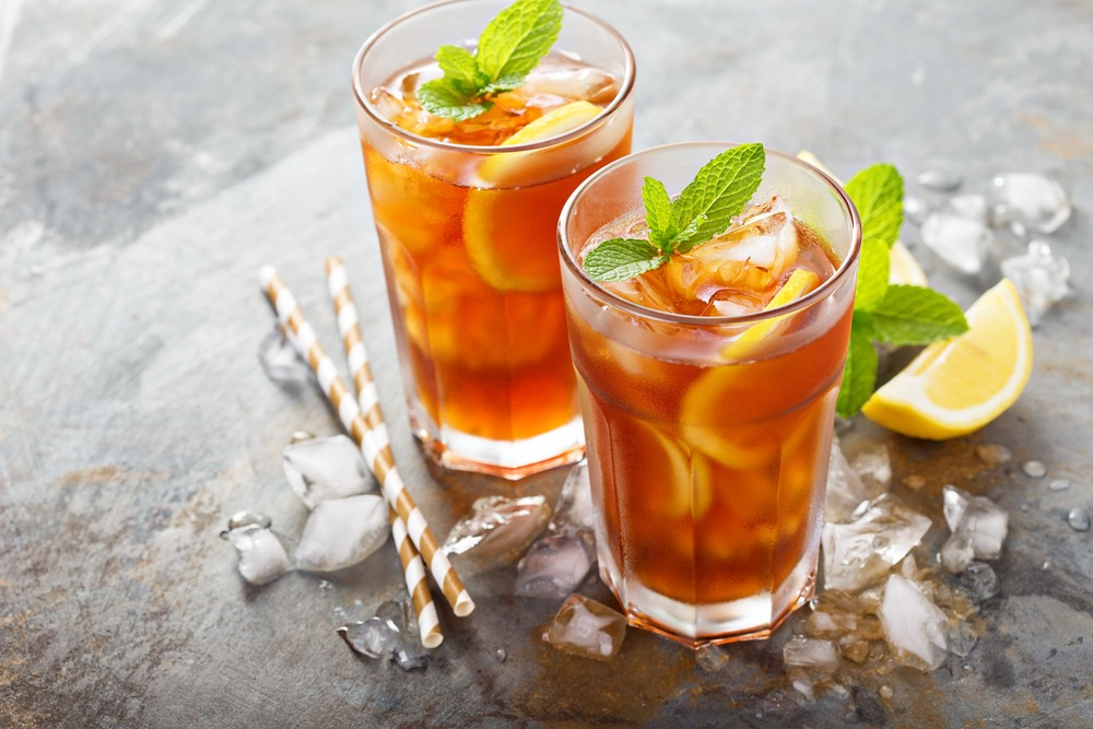 Two glasses of bourbon strawberry iced tea with ice