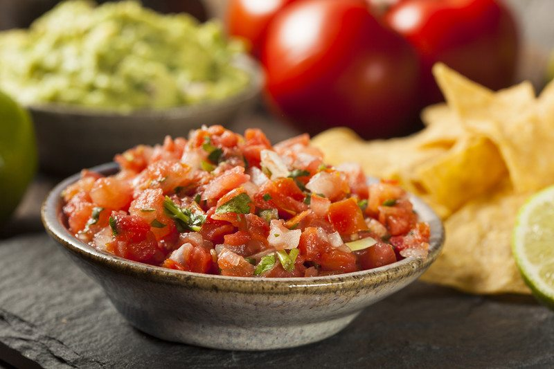 Salsa of the Month Clubs - Shallow stone bowl of fresh salsa, in the background are limes, chips, tomatoes, and guacamole all sitting on a black slate slab