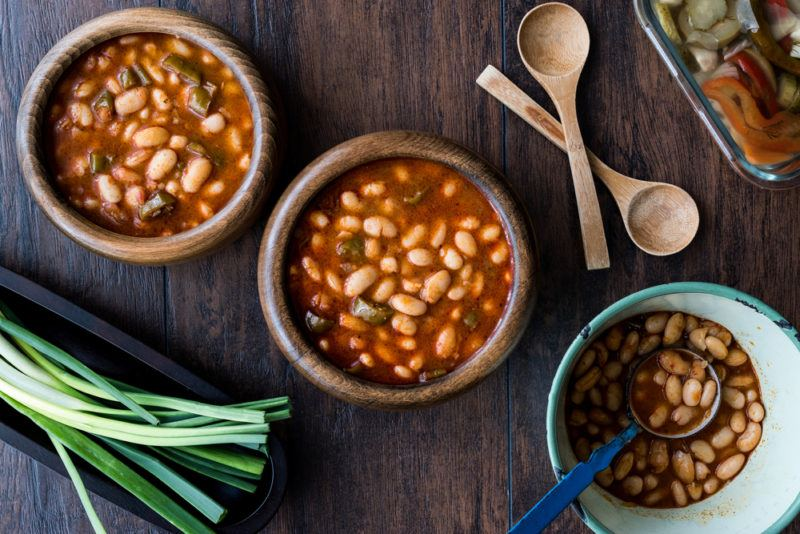 Three wooden bowls containing baked beans