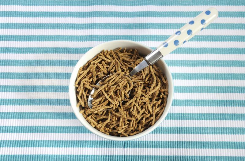 A white bowl that contains a shredded bran cereal with a spoon, on top of a blue and white striped backdrop