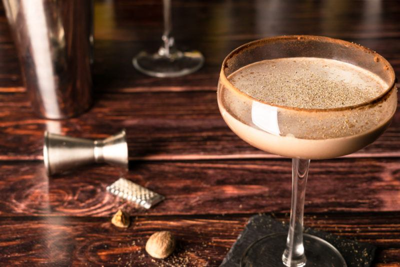 A brandy alexander cocktail on a wooden table with a jigger