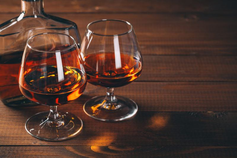 Two glasses and a decanter containing cognac or bourbon