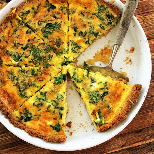 A top down image of a sliced quiche with some pieces missing.