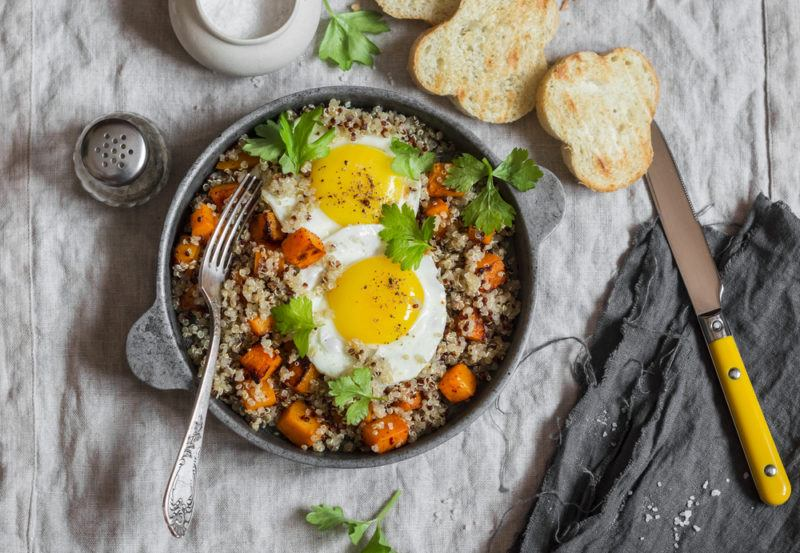 A breakfast bowl with quinoa, eggs. and veggies