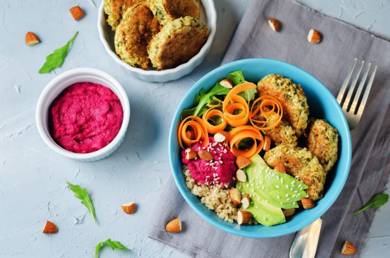 A blue bowl with falafel and beetroot hummus