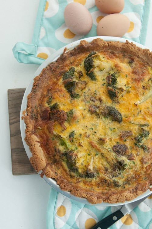 Top down image of a well-cooked quiche in a white pan.