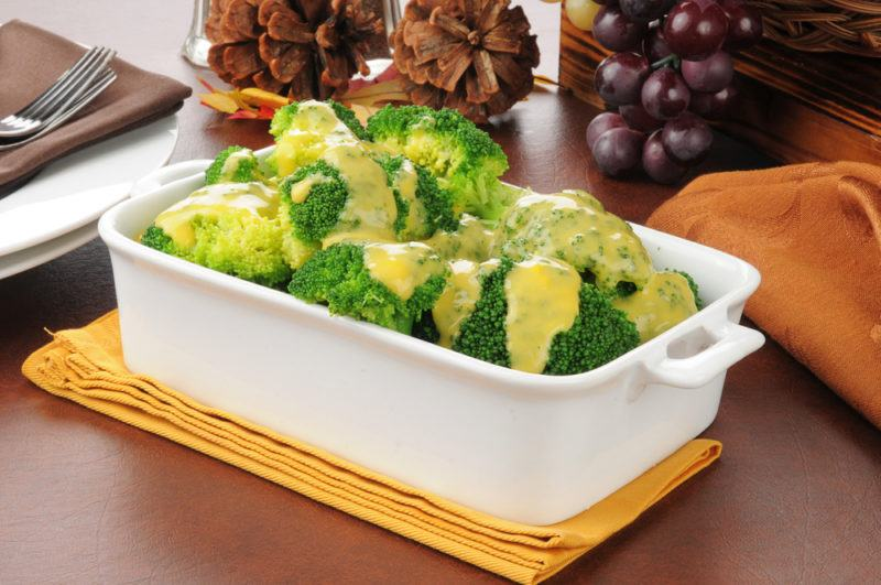 Broccoli with cheese sauce in a white dish