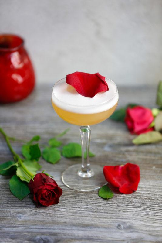 A brown derby cocktail with roses scattered around