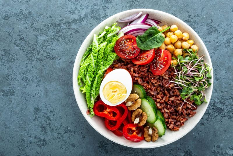 A large white bowl with brown rice, veggies and an egg