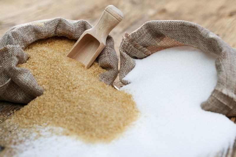 A cloth bag of brown sugar and one of white sugar