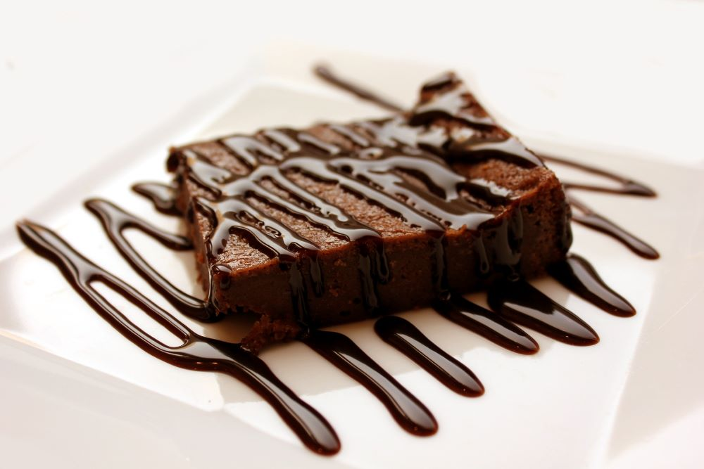 Chocolate brownie with chocolate sauce drizzled diagonally across the brownie and square white plate it sits on