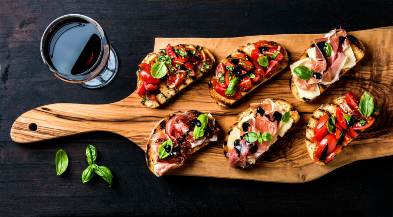 Bruschetta on a wooden board next to a glass of wine