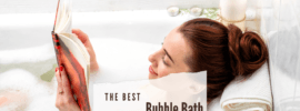 A brown haired woman relaxing in a bath with bubbles and candles