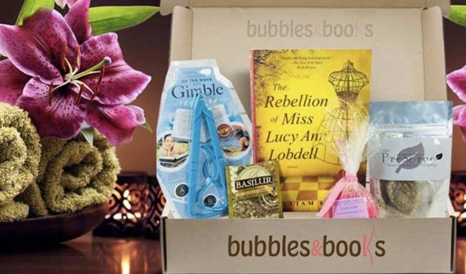 Bubbles and Books box with products for a bath, next to some rolled up towels