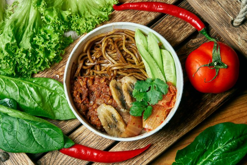 A bowl that includes buckwheat noodles, and fried bananas