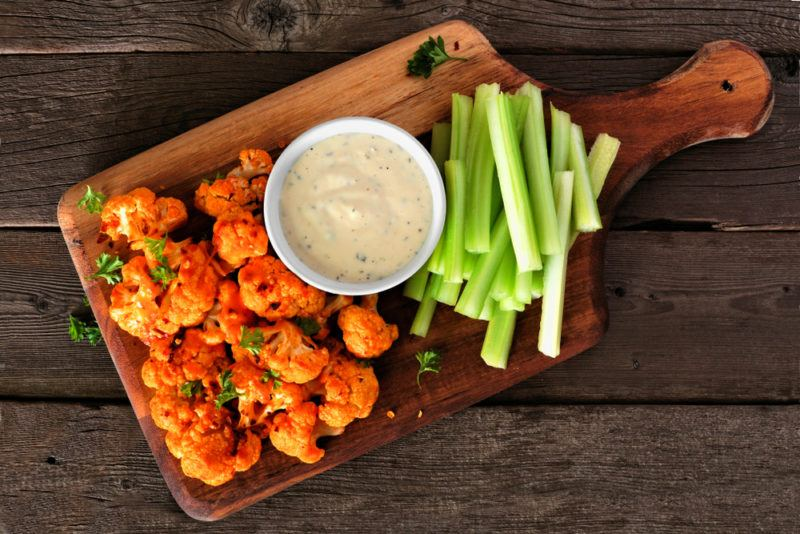 A wooden board with buffalo wings, celery sticks, and dip
