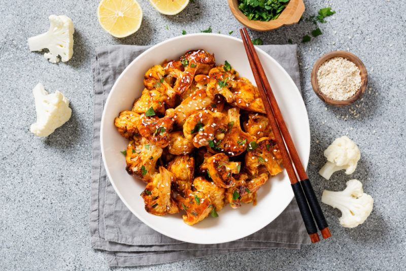 A white plate with buffalo wings made from caulfilower, chopsticks, and pieces of cauliflower scattered around