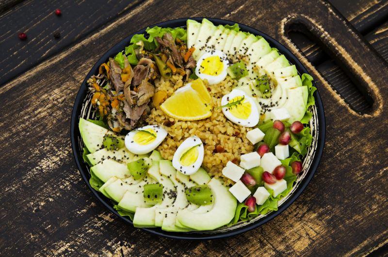 A large black bowl with healthy ingredients like bulgar porridge and beef