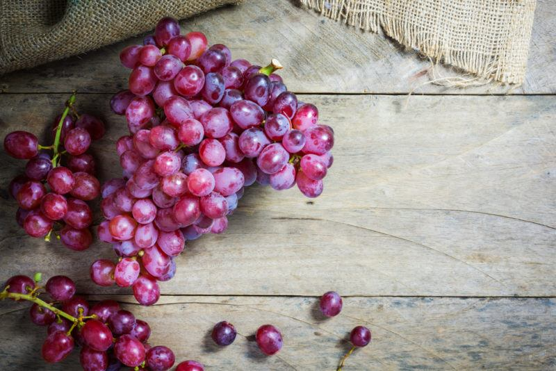 Bunches of red grapes on a wooden table