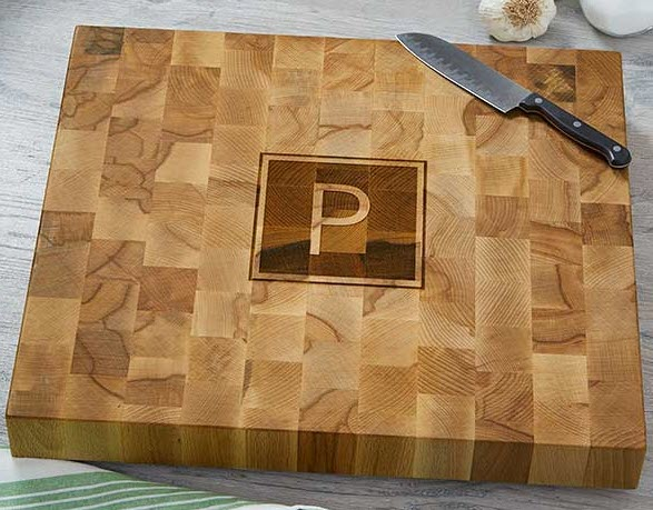 Butcher block cutting board with a P monogrammed into the center.