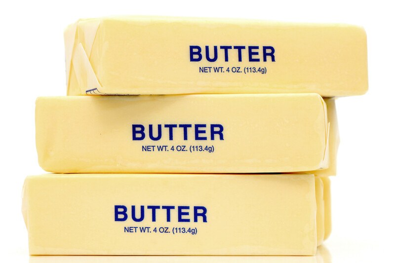 Three cubes of yellow butter in translucent wrappers with blue lettering are stacked on top of each other against a white background.