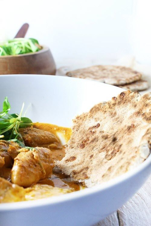 A bowl with butter chicken and a slice of naan bread