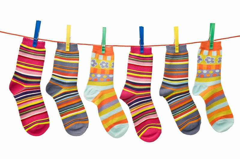 Colorful socks hanging on a clothes line attached with bright colored clothes pins