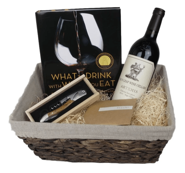 Woven basket with a linen liner and decorative basket fill, sitting on top from left back corner, the What to drink with what to eat book, a bottle of cabernet, a wood handled cork screw and a brown envelope.