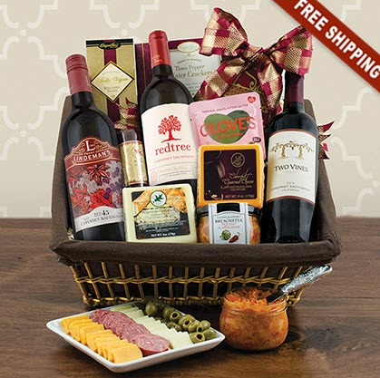 Basket on a wooden table with 3 bottles of wine and various snacks