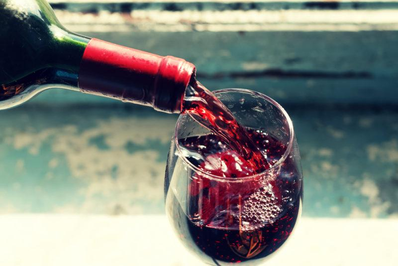 A glass of cabernet sauvignon being poured from a bottle