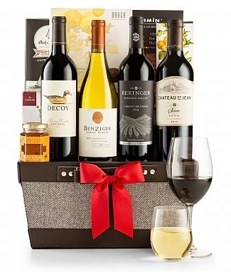 A basket containing 4 bottles of wine and a couple of wine glasses