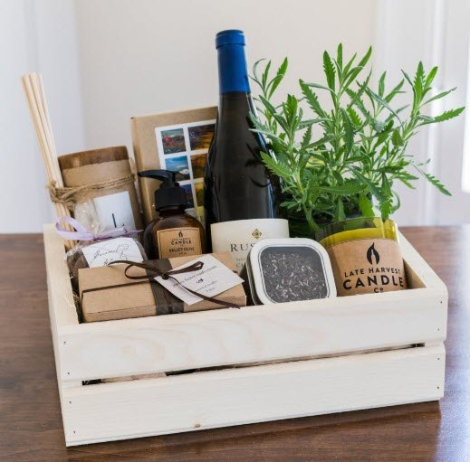 Crate containing white wine, a plant and artisinal goodies