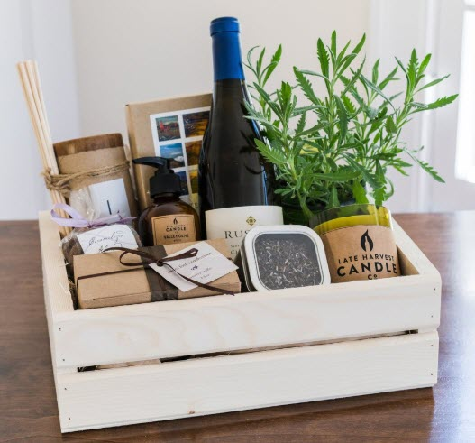 Light wooden box with wine, a candle and a plant
